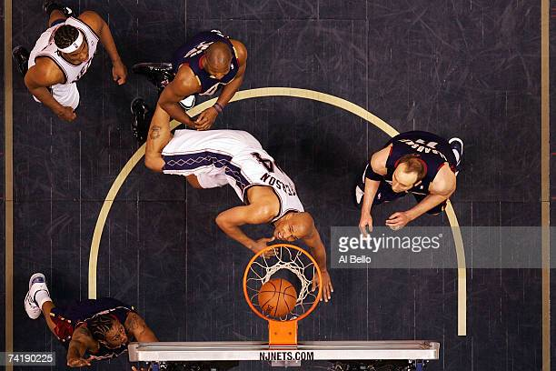 Richard Jefferson of the New Jersey Nets goes to the hoop against Eric Snow and Zydrunas Ilgauskas of the Cleveland Cavaliers during Game Six of the...