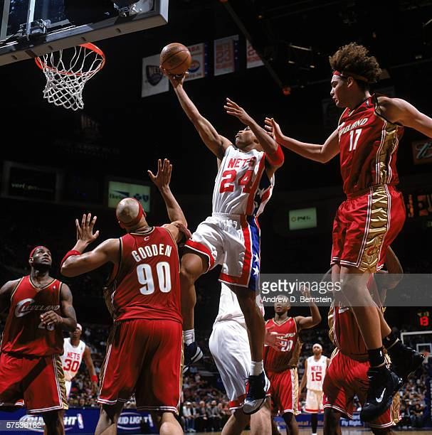 Richard Jefferson of the New Jersey Nets takes the ball to the basket against Drew Gooden and Anderson Varejao of the Cleveland Cavaliers during a...