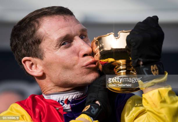 Richard Johnson holds the Gold Cup after riding Native River to victory in the Timico Cheltenham Gold Cup Chase at the Cheltenham Festival at...