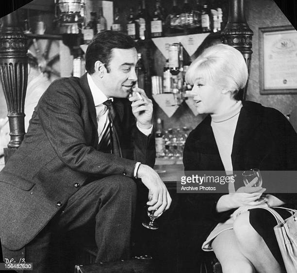 Richard Johnson sits at a bar with Diana Dors in a scene from the film 'Danger Route', 1967.