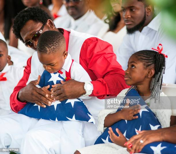 Richard Johnson Sr holds the hand of La David Johnson Jr as he and sister Ah'Leesya Johnson hold folded US flag given to them during the burial...