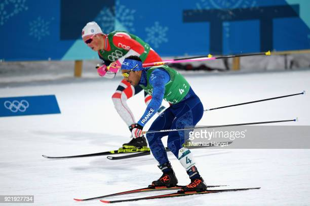 Richard Jouve of France and Johannes Hoesflat of Norway compete during the Cross Country Men's Team Sprint Free semi final on day 12 of the...