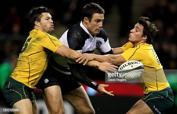 Richard Kahui of the Barbarians offloads as he is tackled by Adam AshleyCooper and Nick Phipps of The Wallabies during the Killik Cup match between...