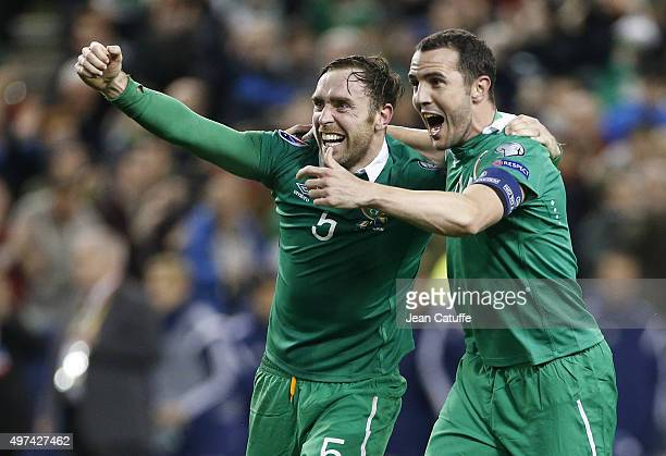 Richard Keogh and John O'Shea of Ireland celebrate victory and qualification for EURO 2016 at the end of the UEFA EURO 2016 qualifier playoff second...