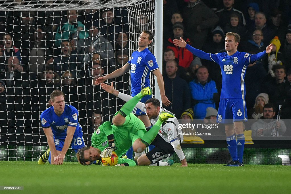 Richard Keogh of Derby County falls under a challenge from Michael Morrison (28) of Birmingham City to earn the match-winning penalty kick during the Sky Bet Championship match between Derby County and Birmingham City at iPro Stadium on December 27, 2016 in Derby, England.