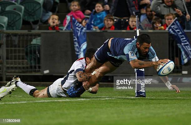 Richard Kingi of the Rebels tackles Rene Ranger of the Blues as he dives over to score a try during the round 10 Super Rugby match between the Blues...