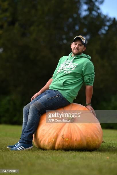 Richard Mann poses for a photograph with his 310.7 kg pumpkin which won its class in the giant vegetable competition on the first day of the...