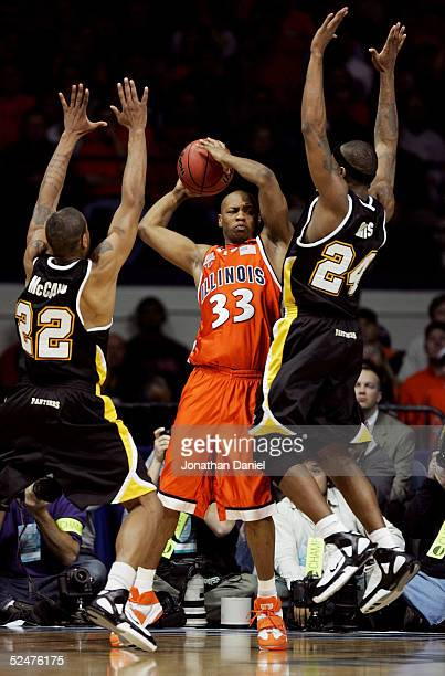 Richard McBride of the Illinois Fighting Illini looks to pass between the defense of Ed McCants and Boo Davis of the WisconsinMilwaukee Panthers in...