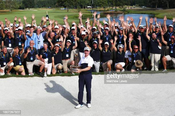 Richard McEvoy of England poses with the trophy and the marshalls / volunteers after his victory on the 18th hole during the final round of the...