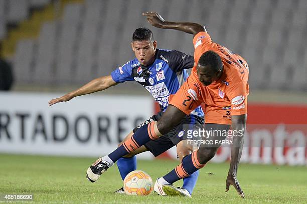 Richard Mercado of Bolivia's Universitario de Sucre vies for ball with Julio Machado of Venezuela's Mineros de Guyana during their 2015 Libertadores...