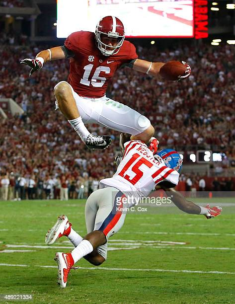 Richard Mullaney of the Alabama Crimson Tide leaps over Kendarius Webster of the Mississippi Rebels on the way to a touchdown at BryantDenny Stadium...