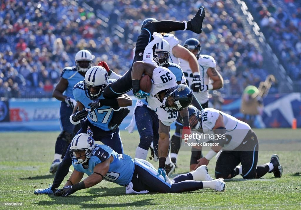 Richard Murphy #39 of the Jacksonville Jaguars is turned head-over-heels by Tommie Campbell #37 and Al Afalava #38 of the Tennessee Titans by at LP Field on December 30, 2012 in Nashville, Tennessee.