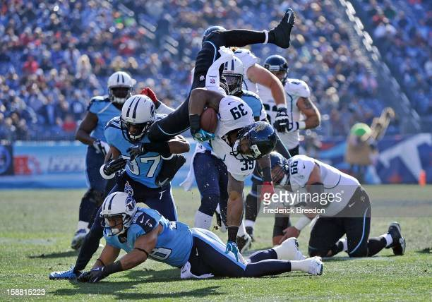Richard Murphy of the Jacksonville Jaguars is turned headoverheels by Tommie Campbell and Al Afalava of the Tennessee Titans by at LP Field on...
