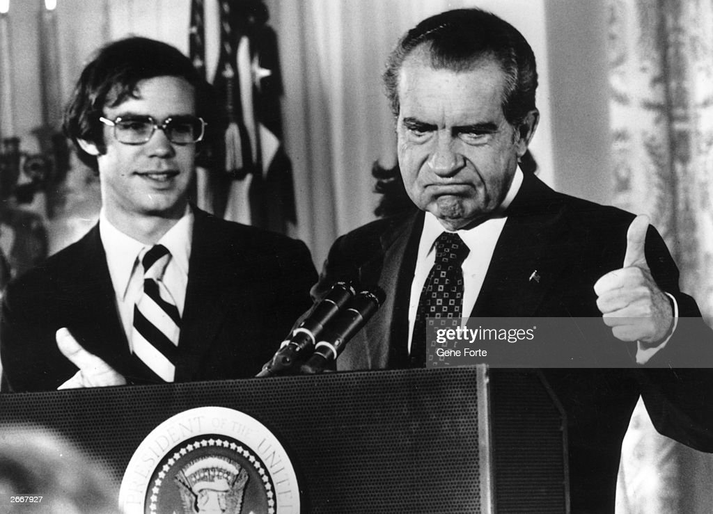 Richard Nixon (1913 - 1994) gives the thumbs up after his resignation as 37th President of the United States. His son-in-law David Eisenhower is with him as he says goodbye to his staff at the White House, Washington DC.