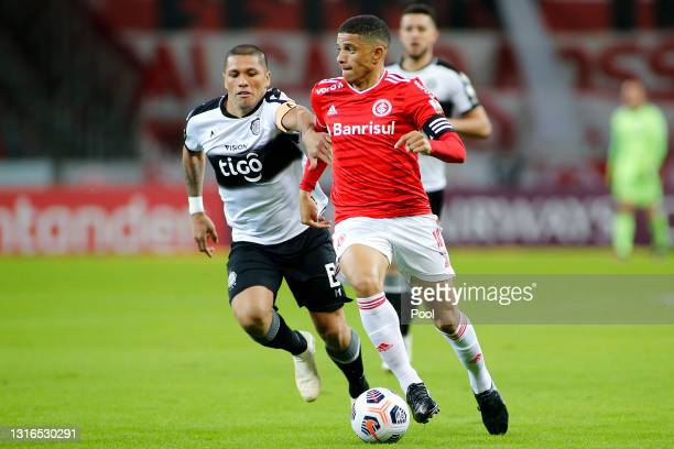 Richard Ortiz of Olimpia competes for the ball with Taison of Internacional during a match between Internacional and Olimpia as part of Group B of...