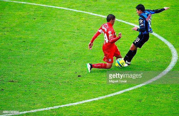 Richard Ortiz of Toluca fights for the ball with Antonio Naelson of Queretaro during a match between Toluca and Queretaro as part of 10th round...