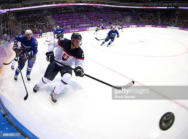 Richard Panik of Slovakia and Ales Kranjc of Slovenia go after a puck bouncing off the glass in the third period during the Men's Ice Hockey...