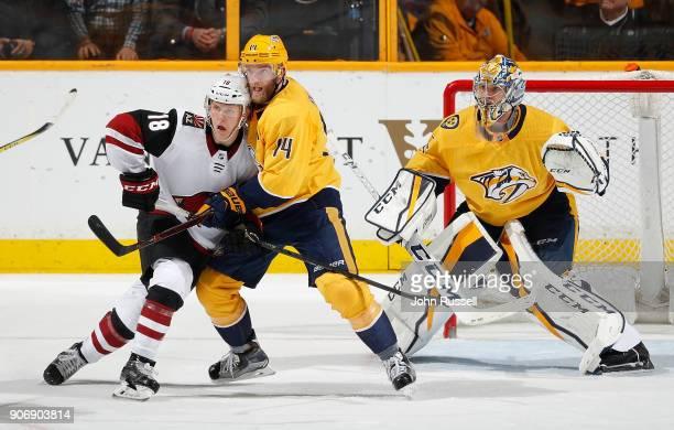 Richard Panik of the Arizona Coyotes battles against Mattias Ekholm of the Nashville Predators in front of goalie Pekka Rinne during an NHL game at...
