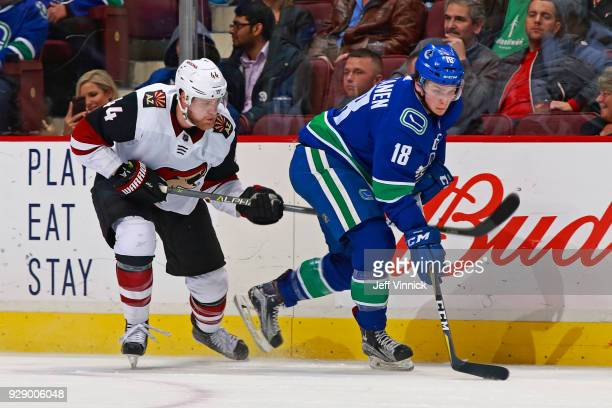 Richard Panik of the Arizona Coyotes checks Jake Virtanen of the Vancouver Canucks during their NHL game at Rogers Arena March 7 2018 in Vancouver...