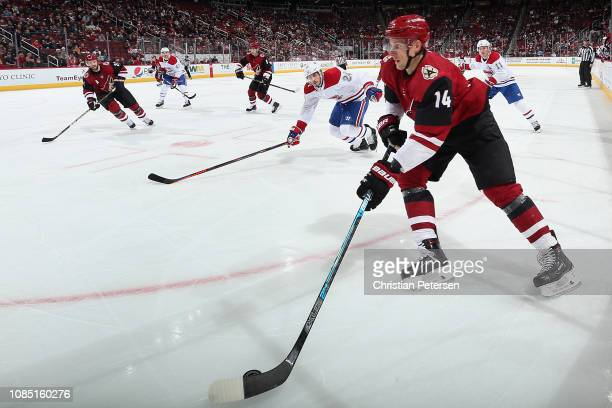 Richard Panik of the Arizona Coyotes skates with the puck ahead of Phillip Danault of the Montreal Canadiens during the third period of the NHL game...