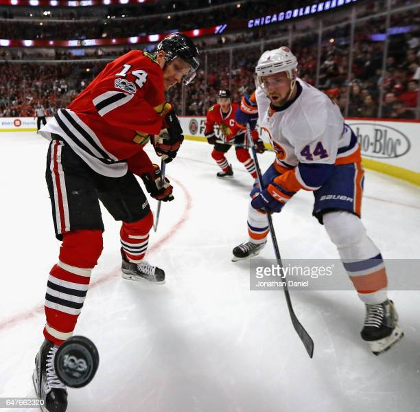 Richard Panik of the Chicago Blackhawks and Calvin de Haan of the New York Islanders battle for the puck in the corner at the United Center on March...