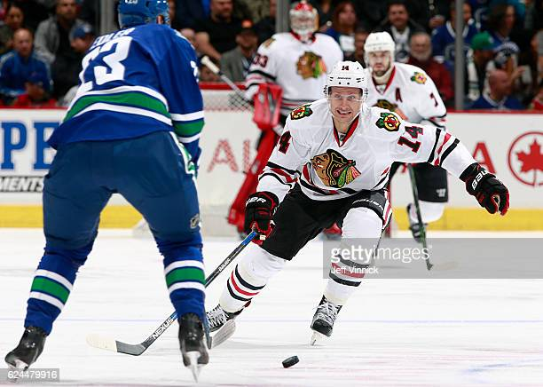 Richard Panik of the Chicago Blackhawks moves to check Alexander Edler of the Vancouver Canucks during their NHL game at Rogers Arena November 19,...