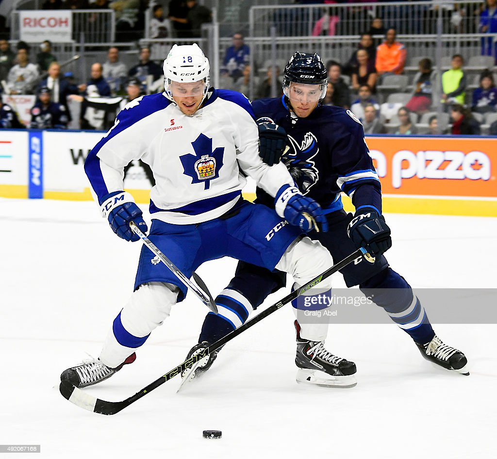 Richard Panik #18 of the Toronto Marlies battles with Jan Kostalek #3 of the Manitoba Moose during Opening Night AHL game action on October 9, 2015 at the Ricoh Coliseum in Toronto, Ontario, Canada.