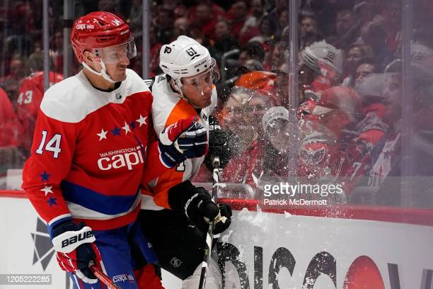 Richard Panik of the Washington Capitals and Justin Braun of the Philadelphia Flyers collide in the third period at Capital One Arena on March 04,...