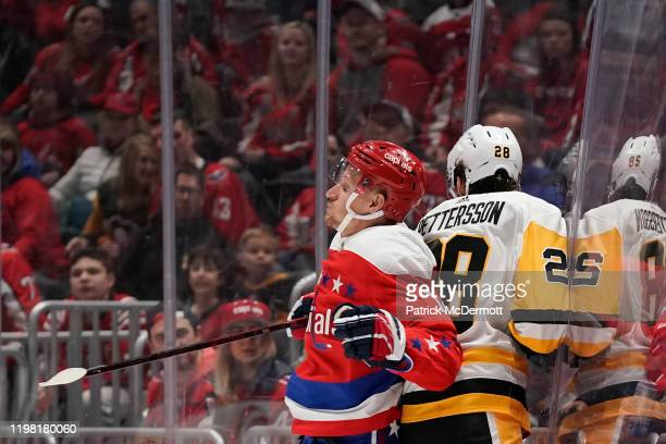 Richard Panik of the Washington Capitals and Marcus Pettersson of the Pittsburgh Penguins collide in the third period at Capital One Arena on...