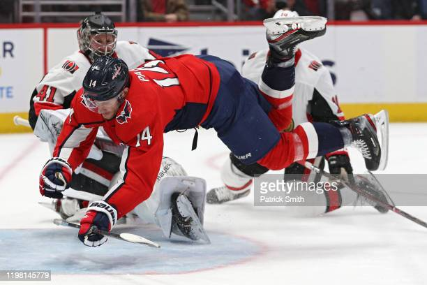 Richard Panik of the Washington Capitals is tripped up by goalie Craig Anderson of the Ottawa Senators during the second period at Capital One Arena...