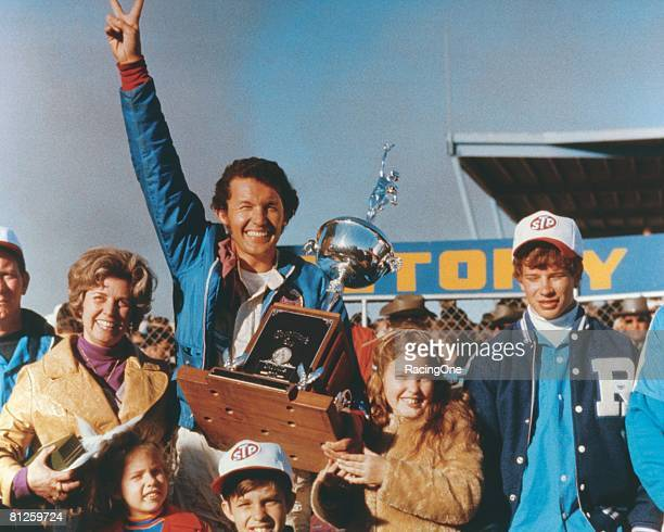 Richard Petty driver of the STP Plymouth celebrates in victory lane with his wife Lynda daughters Sharon and Lisa and son Kyle after winning the...