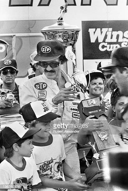 Richard Petty driver of the STP Pontiac celebrates in Victory Lane at the Daytona International Speedway on July 4 1984 in Daytona Beach Florida...