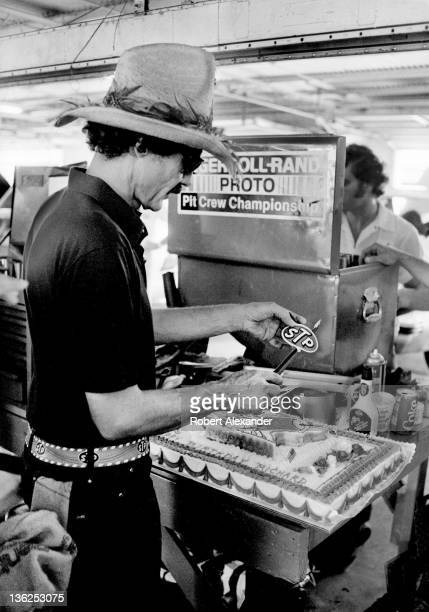 Richard Petty driver of the STP Pontiac cuts his birthday cake in the Daytona International Speedway garage prior to the 1986 Firecracker 400 on July...