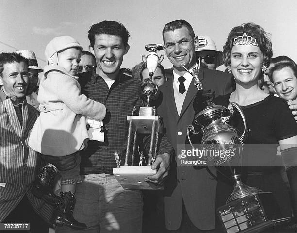 Richard Petty holds his infant son Kyle after winning the Gwyn Staley Memorial 250 at North Wilkesboro Speedway in 1962 Making the presentation are...