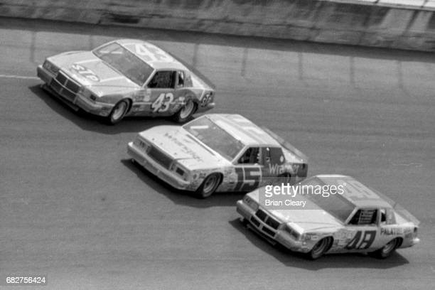 Richard Petty in the Pontiac LeMans Dale Earnhardt in the Ford Thunderbird and James Hylton in the Buick Regal race 3wide during the Firecracker 400...