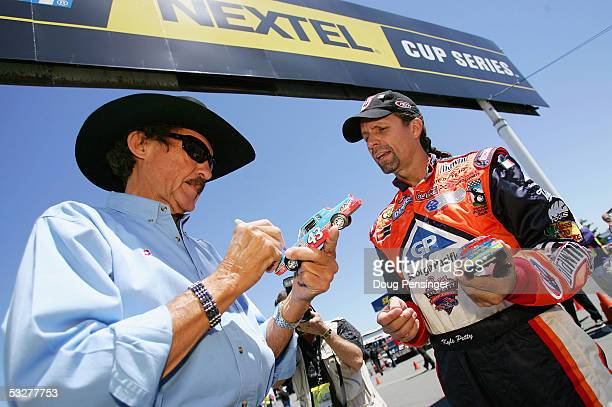 Richard Petty, left, and his son Kyle Petty, driver of the Kyle Petty Charity Ride\Brawny Dodge, sign autgraphs for fans during qualifying for the...