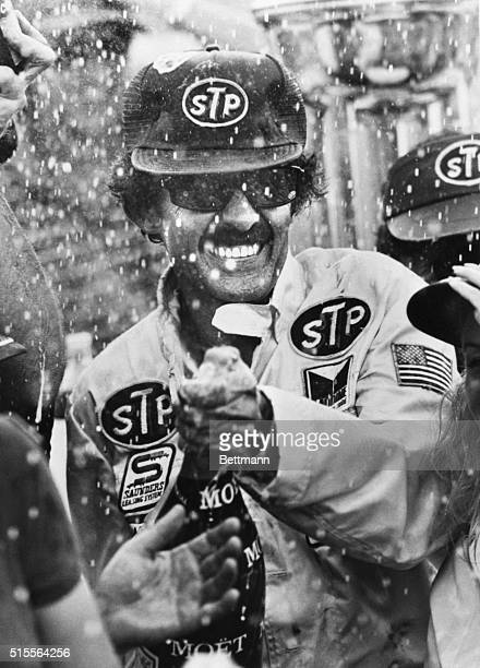 Richard Petty smiles as he sprays champagne in the victory circle at the Daytona International Speedway 7/4 after winning the Fire-cracker 400, his...