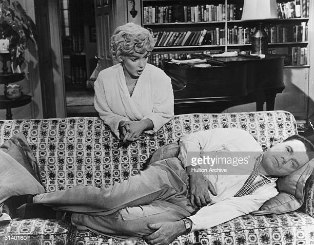 Richard played by Tom Ewell lies on a sofa hugging his stomach whle a sympathetic Marily Monroe playing 'The Girl' leans over him A scene from 'The...