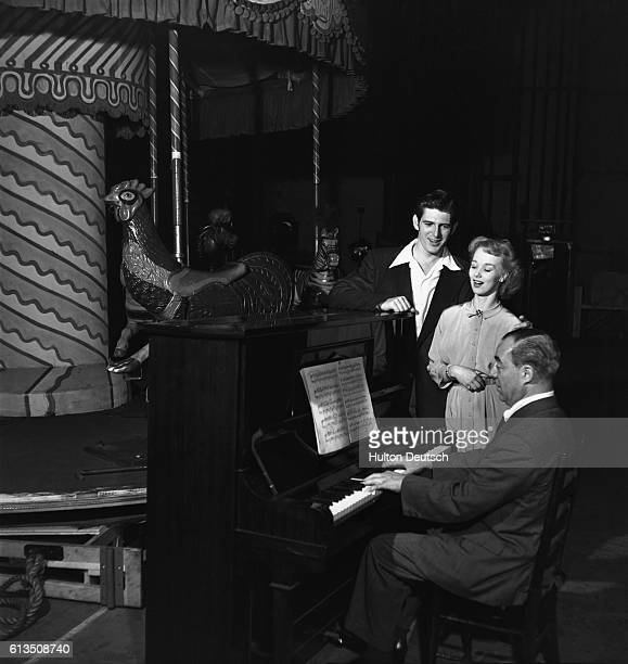 Richard Rodgers the American composer playing the piano to accompany two singers at a rehearsal for his musical Carousel running in London