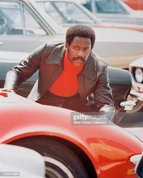 Richard Roundtree, US actor, crouching behind a red sports car in a publicity still issued for the film, 'Shaft', 1971. The blaxploitation film,...