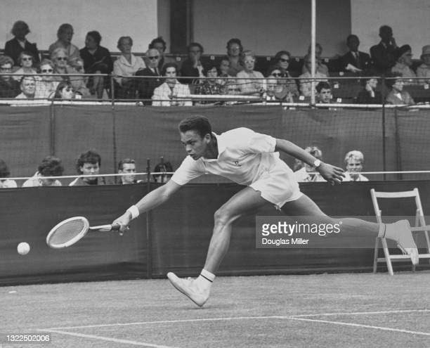 Richard Russell of Jamaica reaches to make a running forehand return to Stanley Matthews of Great Britain during their Men's Singles First Round...