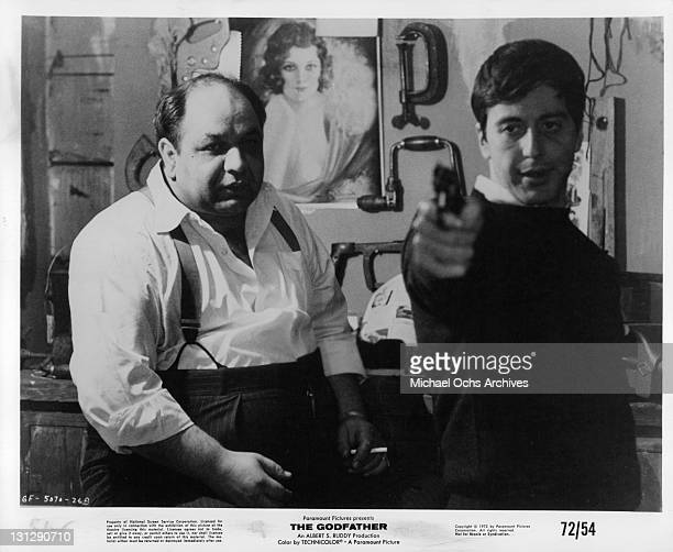 Richard S Castellano watching Al Pacino aim gun in a scene from the film 'The Godfather' 1972