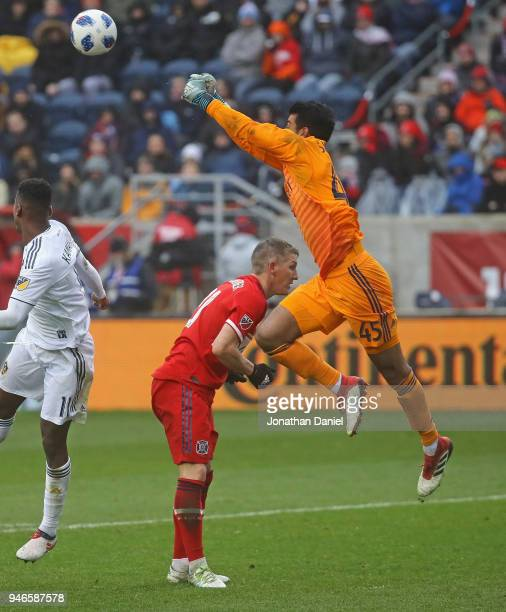 Richard Sanchez of the Chicago Fire leaps over teammate Bastian Schweinsteiger and Ola Kamara of Los Angeles Galaxy to make a save at Toyota Park on...