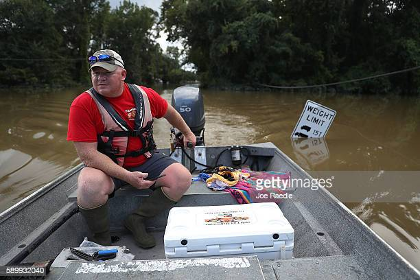 Richard Schafer navigates a boat down a flooded road on August 15, 2016 in Baton Rouge, Louisiana. Record-breaking rains pelted Louisiana over the...