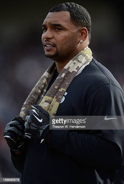 Richard Seymour Oakland Raiders not in uniform against the New Orleans Saints looks on from the sidelines during an NFL football game at Oco Coliseum...