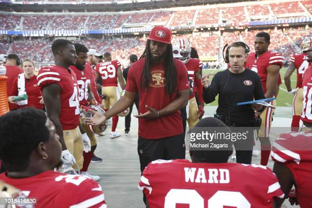 Richard Sherman and Defensive Backs Coach Jeff Hafley of the San Francisco 49ers talk with the defensive backs on the sideline during the game...