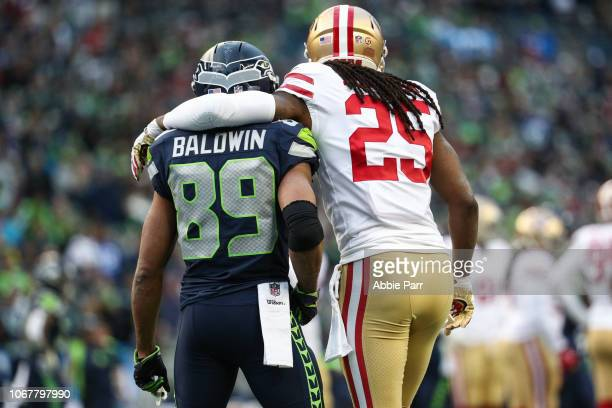 Richard Sherman of the San Francisco 49ers puts his arm around former teammate Doug Baldwin of the Seattle Seahawks in the third quarter at...