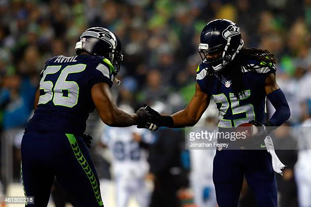 Richard Sherman of the Seattle Seahawks celebrates with Cliff Avril after intercepting a ball intended for Philly Brown of the Carolina Panthers...