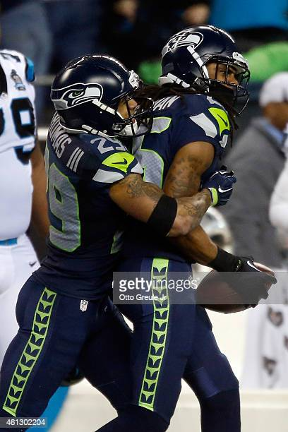 Richard Sherman of the Seattle Seahawks celebrates with Earl Thomas after intercepting a ball intended for Philly Brown of the Carolina Panthers...