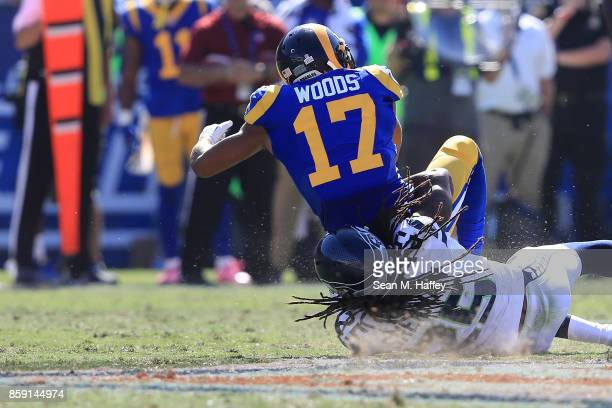 Richard Sherman of the Seattle Seahawks tackles Robert Woods of the Los Angeles Rams during the game at the Los Angeles Memorial Coliseum on October...